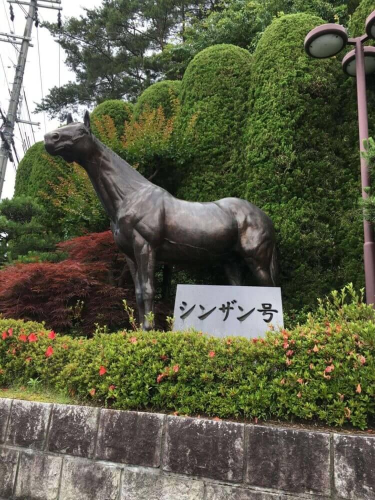 栗東トレセン入り口に立つシンザン像