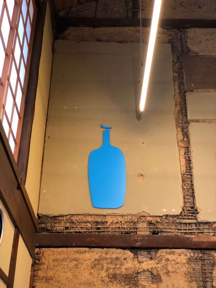 物販スペースの土壁にブルーボトルのシンボルマークが