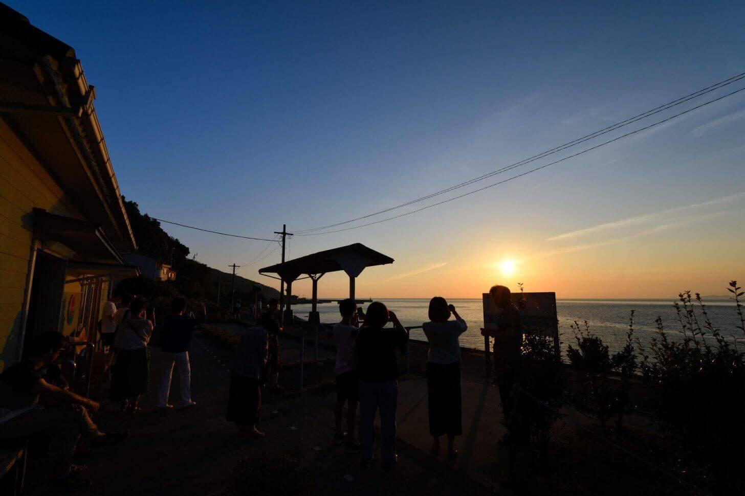 たくさんの人が見守る下灘駅の夕日